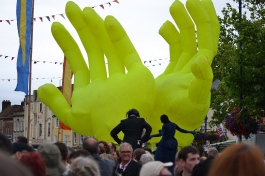Giant inflatable hands from Neighbourhood Watch Stilts International passing through the crowd at the main stage